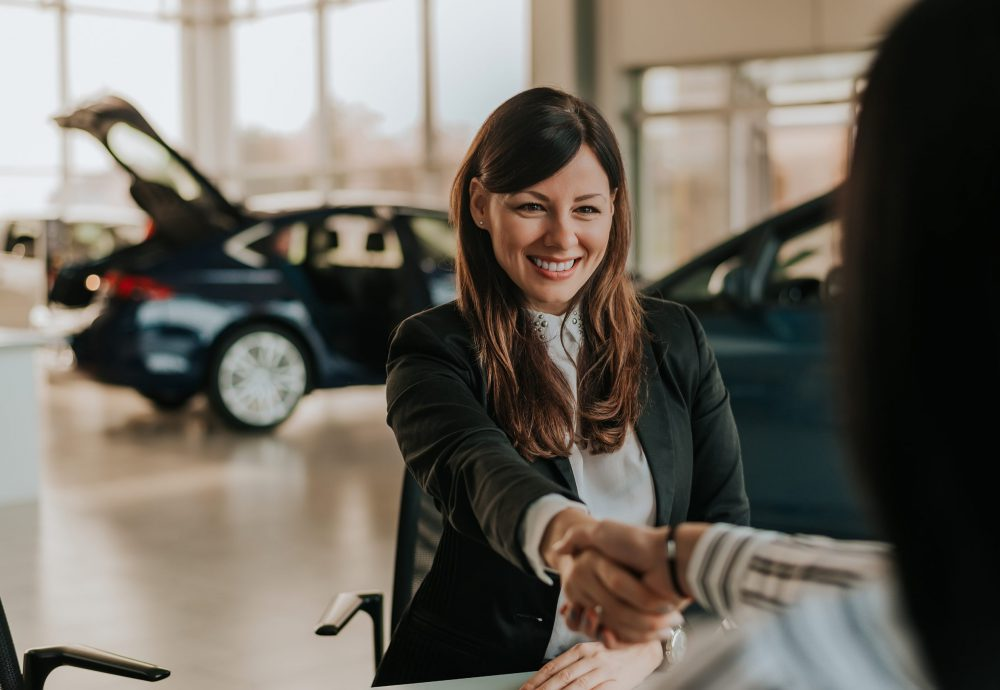 Car dealer shaking hand with a customer in a car shop.