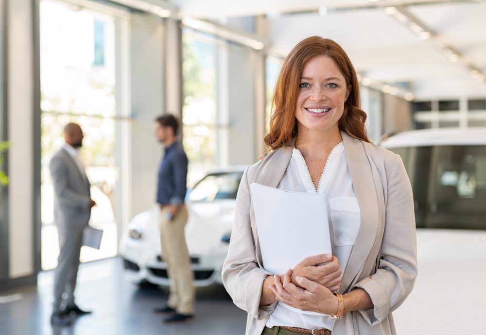 Smiling saleswoman holding document while looking at camera at car showroom. Young cardealer holding clipboard in automobile showroom. Professional confident sales person working in modern car dealership.